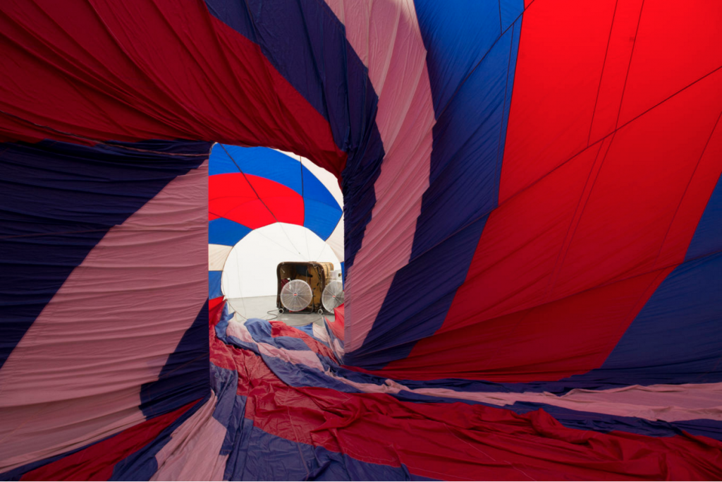 A red, white, and blue fabric canopy presses against walls of room; portable fans blow air into the room through a doorway